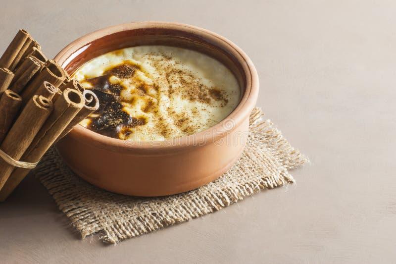 Gebackenes türkisches sutlac Nachtisch des Reispuddings in der Töpferwarenkasserolle mit Zimtstangen stockfotos