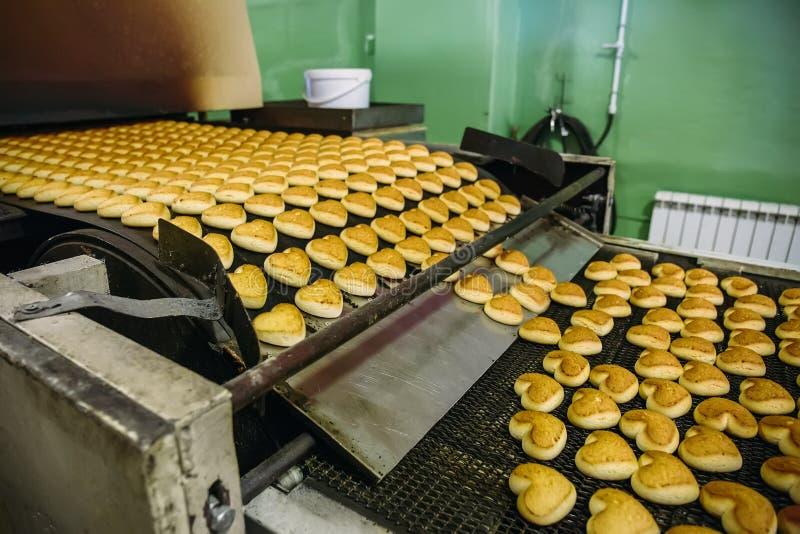 Gebakje op transportbandlijn, de fabriek van de voedselproductie of installatie met machines Het maken van koekjesproces stock fotografie