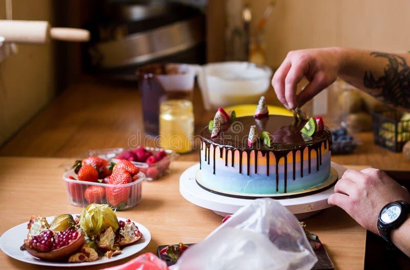 Gebakjechef-kok in de keuken die een cake van chocolade, fruit verfraaien, royalty-vrije stock fotografie
