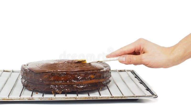 Gebakjechef-kok die definitieve aanrakingen maken aan een cake van de sacherchocolade royalty-vrije stock fotografie