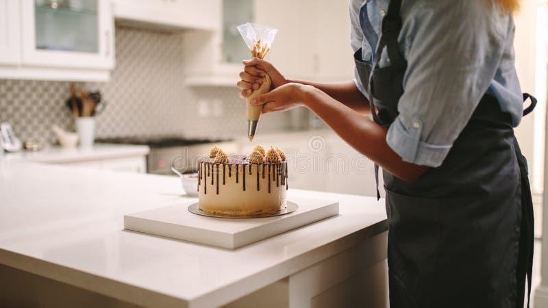 Gebakjechef-kok die een cake verfraaien royalty-vrije stock afbeeldingen