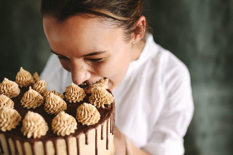 Gebakjechef-kok die gehele cake eten stock foto