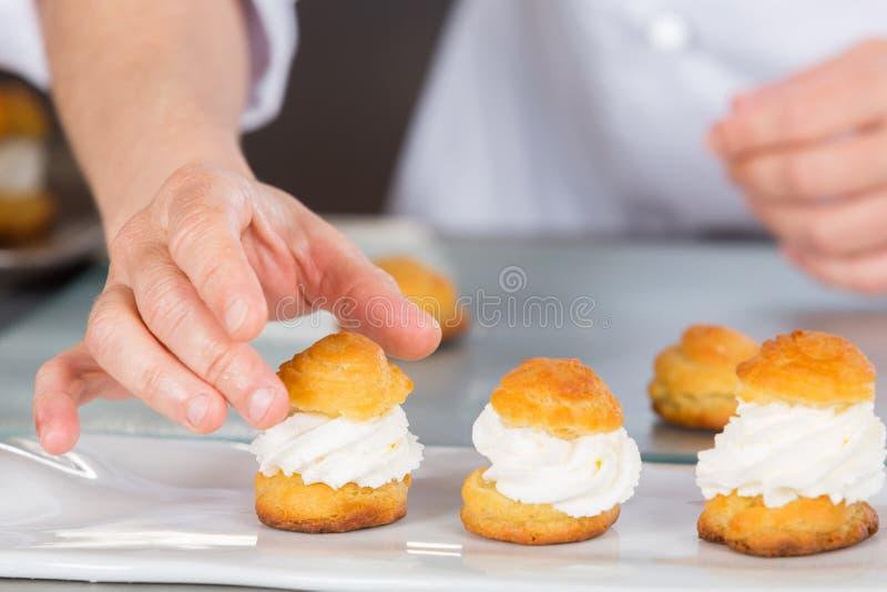 Gebakjechef-kok met profiteroles stock foto
