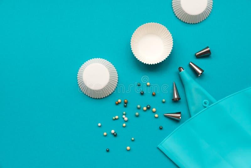 Gebakjezak, cupcake gevallen en suiker die op blauwe pastelkleurachtergrond bestrooien Hoogste mening Vlak leg De ruimte van het  stock foto's