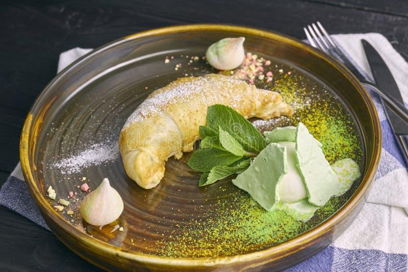 Gebakken appelstrudel met een lepel van vanilleroomijs en schuimgebakje op een donkere houten lijst, close-up restaurant dienend  royalty-vrije stock foto