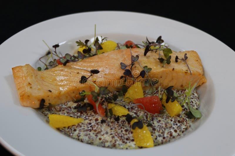 Gebakken Atlantische zalm met romige quinoa en citrusvruchtensegmenten royalty-vrije stock afbeeldingen