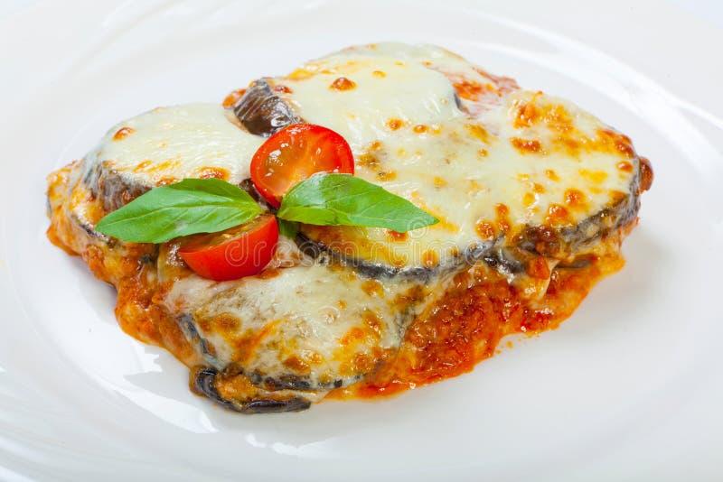 Gebakken aubergine met kaas, tomaten en kruiden op een witte plaat Een schotel van aubergine is op een houten lijst stock foto's