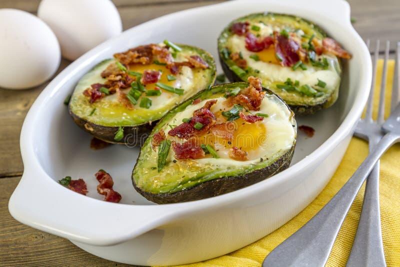 Gebakken avocado's en eieren met bacon en bieslook stock afbeeldingen