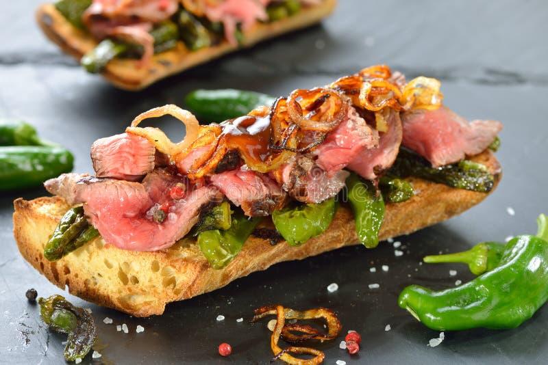 Gebakken baguette met Spaanse pepers en lapje vlees royalty-vrije stock afbeeldingen