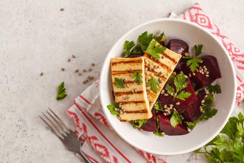 Gebakken bietensalade met geroosterde tofu peterselie en olie in wit BO stock afbeelding