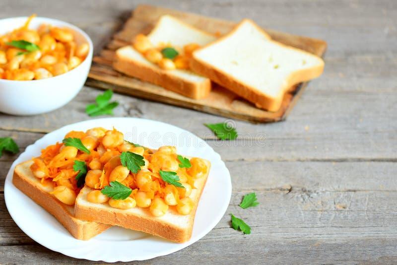 Gebakken bonen met groenten op wit brood en op plaat Gebakken witte bonen in een kom, broodplakken, peterselietwijgen stock foto's