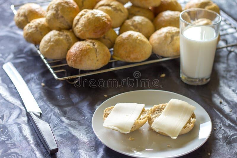 Gebakken brood en broodjes met kaas en glas melk stock fotografie