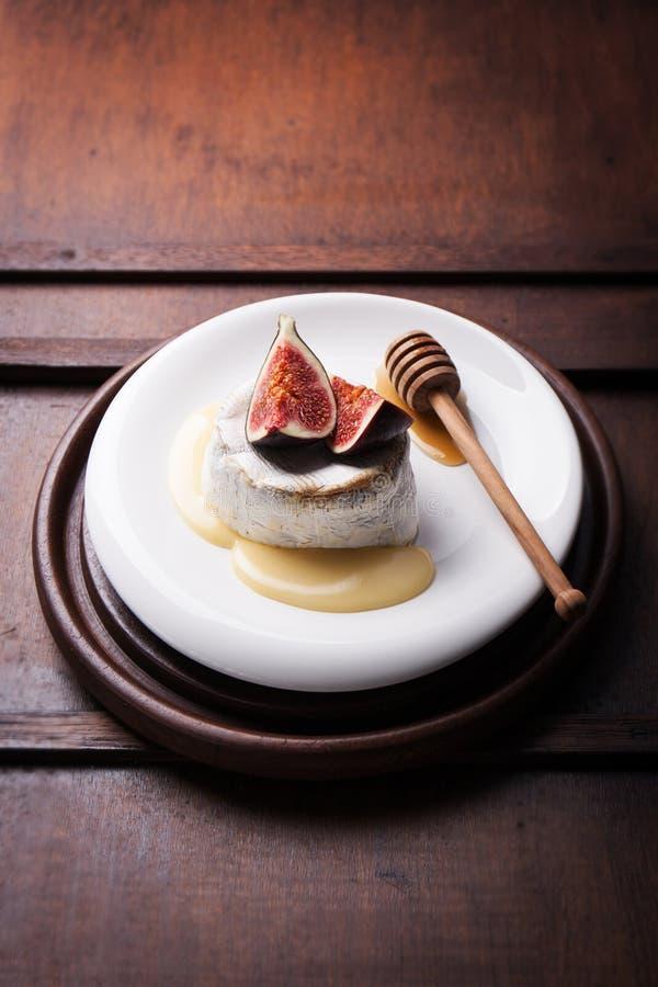 Gebakken Camembert met verse fig. en honing op een houten achtergrond stock fotografie