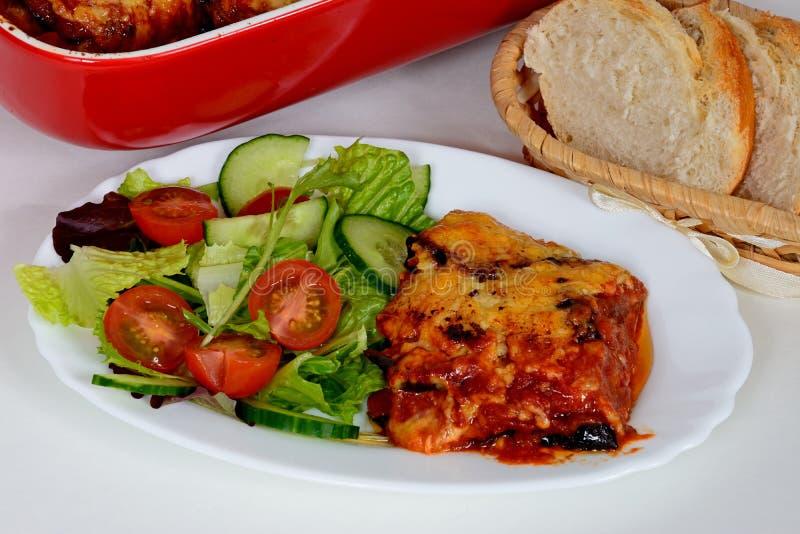 Gebakken die aubergine met kaas wordt en met salade wordt gediend bedekt die stock afbeelding