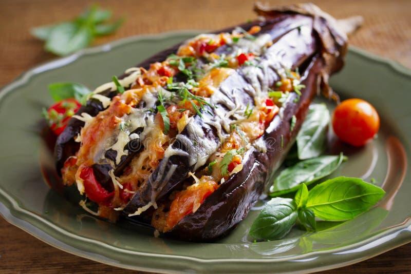 Gebakken die aubergine, met vlees wordt gevuld, tomaten, paprika, ui en kaas Aubergine met vlees en groenten stock afbeeldingen