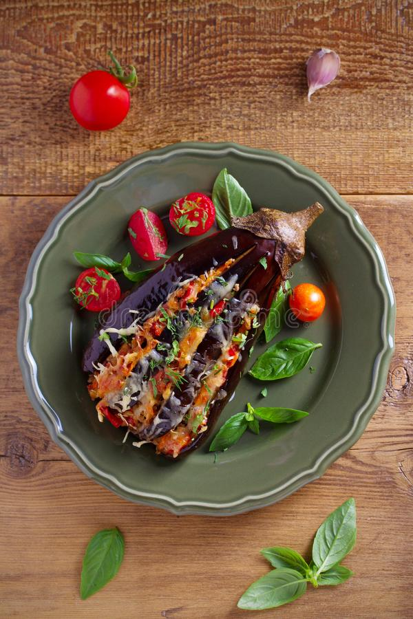 Gebakken die aubergine, met vlees wordt gevuld, tomaten, paprika, ui en kaas Aubergine met vlees en groenten stock afbeelding