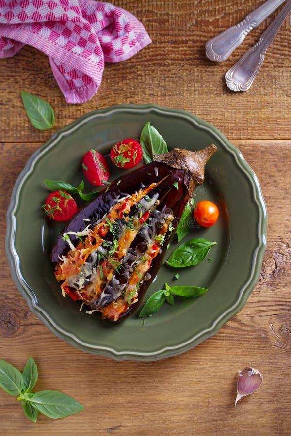 Gebakken die aubergine, met vlees wordt gevuld, tomaten, paprika, ui en kaas Aubergine met vlees en groenten stock foto's