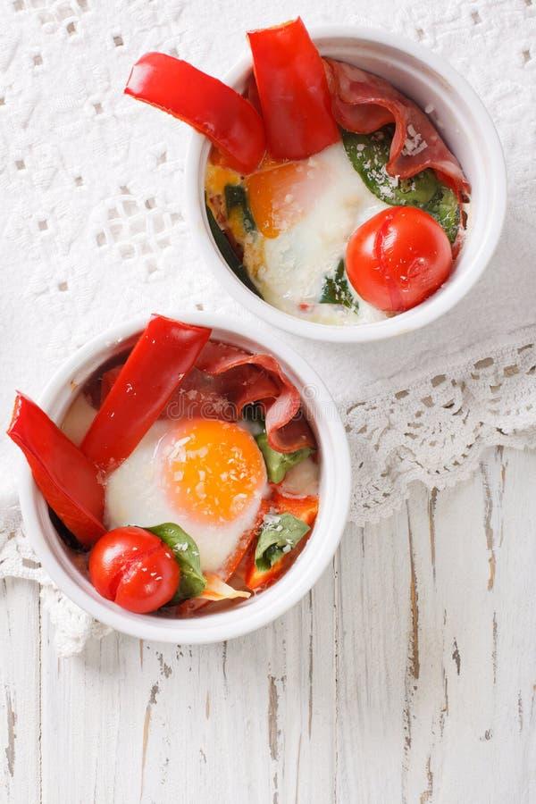 Gebakken ei met spinazie, peper, tomaten en kaas in kopcl royalty-vrije stock afbeeldingen