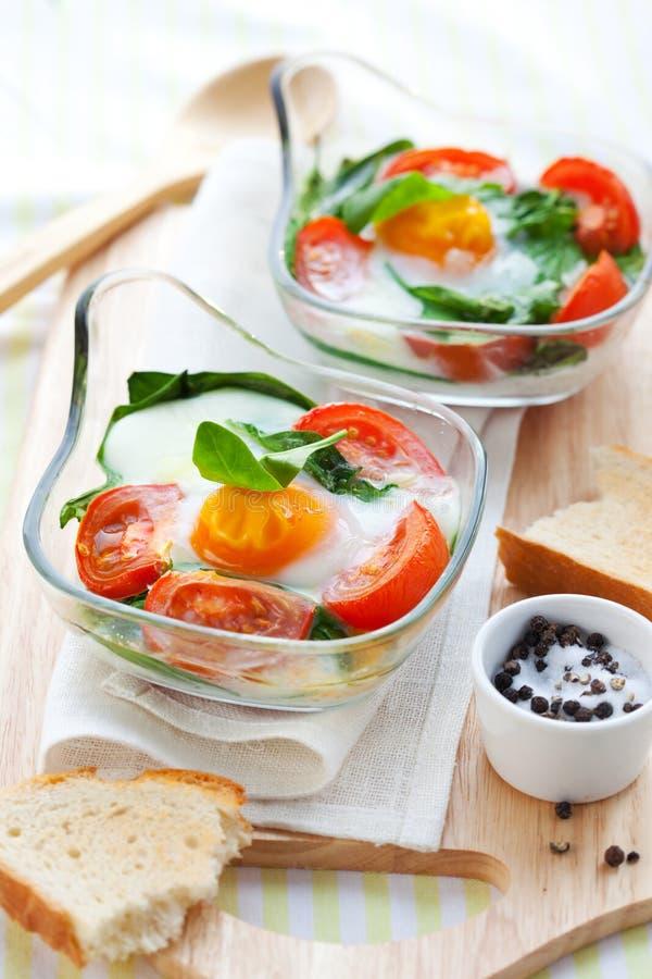 Gebakken ei met tomaten en spinazie stock foto's