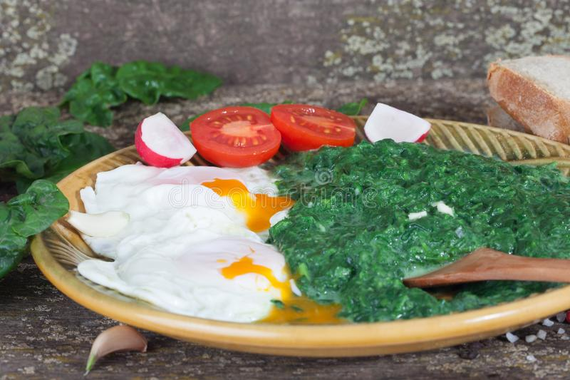 Gebakken eieren met spinazie en tomaten stock afbeelding