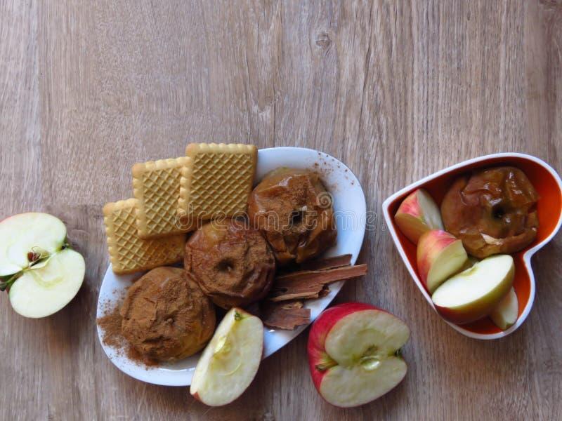 Gebakken en fress appelen, koekjes, en kaneel op de rustieke achtergrond van het stijl eiken hout Licht bio organisch ontbijt stock foto's