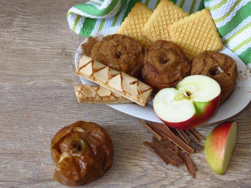 Gebakken en verse appelen, koekjes, en kaneelschors op de rustieke achtergrond van het stijl eiken hout Licht bio organisch ontbi stock fotografie