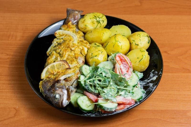 Gebakken forel met citroen op een plaat met arugula, tomaat, komkommersalade en jonge aardappels met dille royalty-vrije stock afbeelding