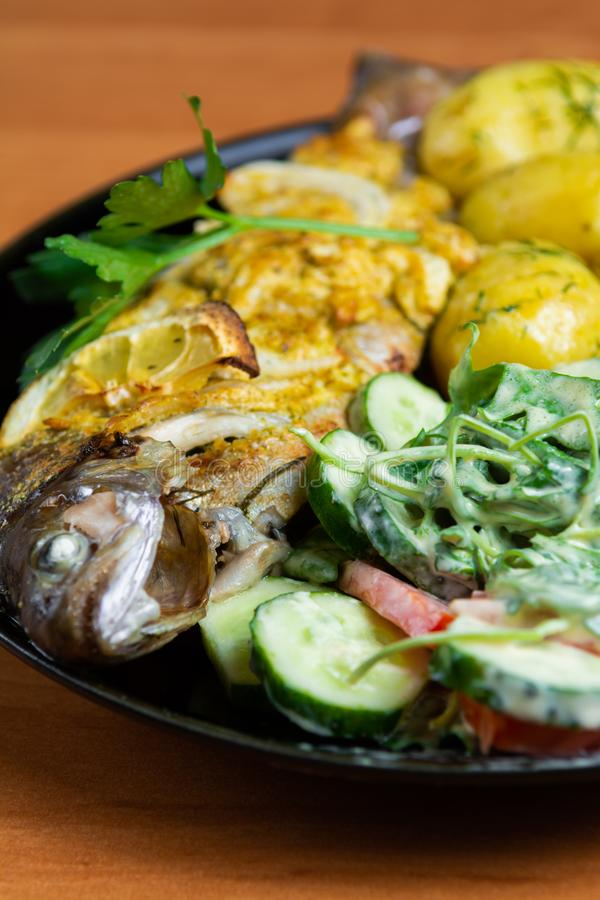 Gebakken forel met citroen op een plaat met arugula, tomaat, komkommersalade en jonge aardappels met dille royalty-vrije stock fotografie