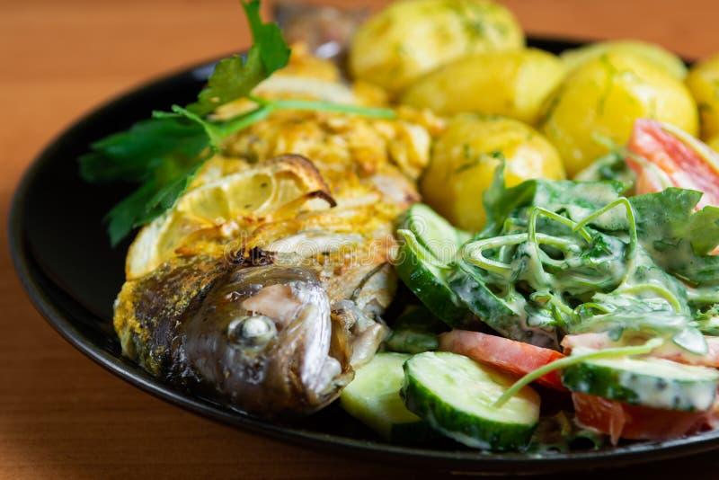 Gebakken forel met citroen op een plaat met arugula, tomaat, komkommersalade en jonge aardappels met dille stock afbeelding