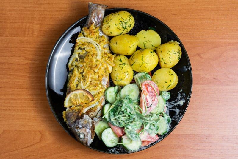 Gebakken forel met citroen op een plaat met arugula, tomaat, komkommersalade en jonge aardappels met dille stock foto's