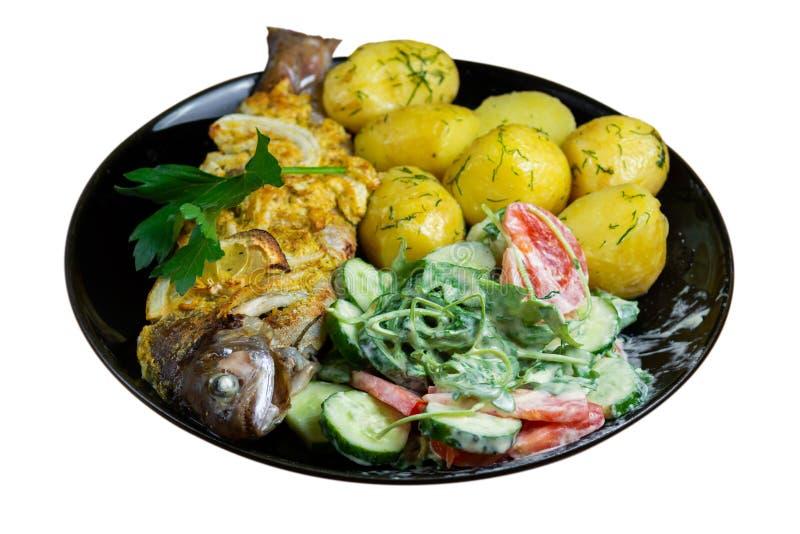 Gebakken forel op een plaat met een salade van arugula, tomaten, komkommers en jonge die aardappels met dille op witte achtergron stock foto