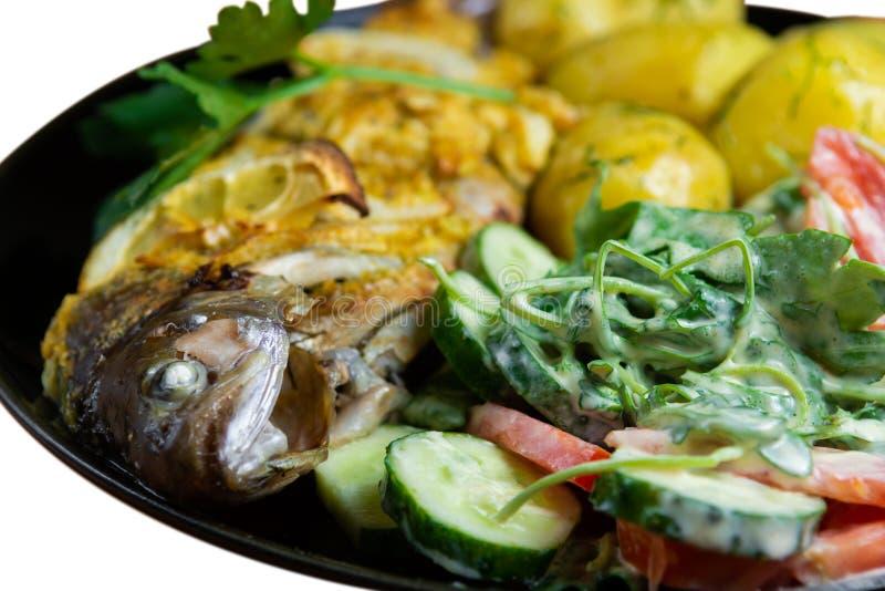 Gebakken forel op een plaat met een salade van arugula, tomaten, komkommers en jonge die aardappels met dille op witte achtergron royalty-vrije stock fotografie