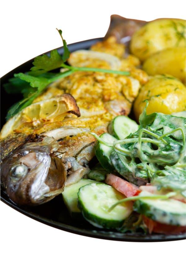 Gebakken forel op een plaat met een salade van arugula, tomaten, komkommers en jonge die aardappels met dille op witte achtergron stock afbeelding