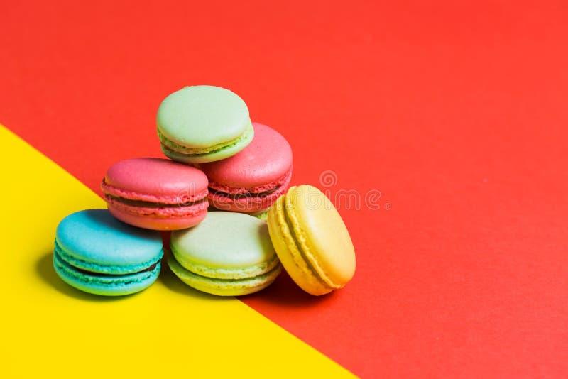 Gebakken Franse multicolored makarons op rode en gele achtergrond met exemplaarruimte stock afbeeldingen