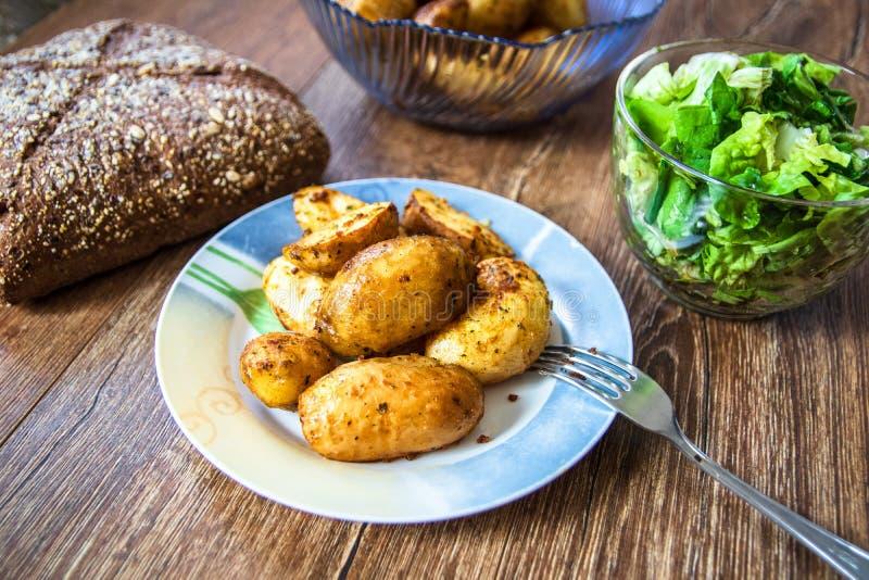 Gebakken jonge aardappels op een plaat, een eigengemaakte gehele korrelbrood en een slasalade royalty-vrije stock foto's