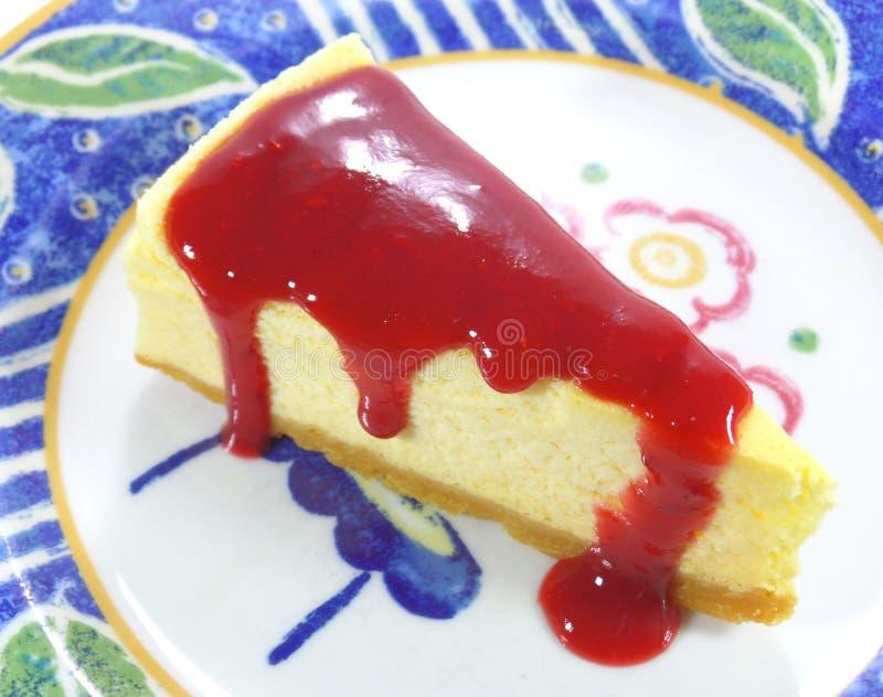 Gebakken kaastaart met rode die frambozensaus op witte en blauwe plaat wordt gediend stock afbeeldingen