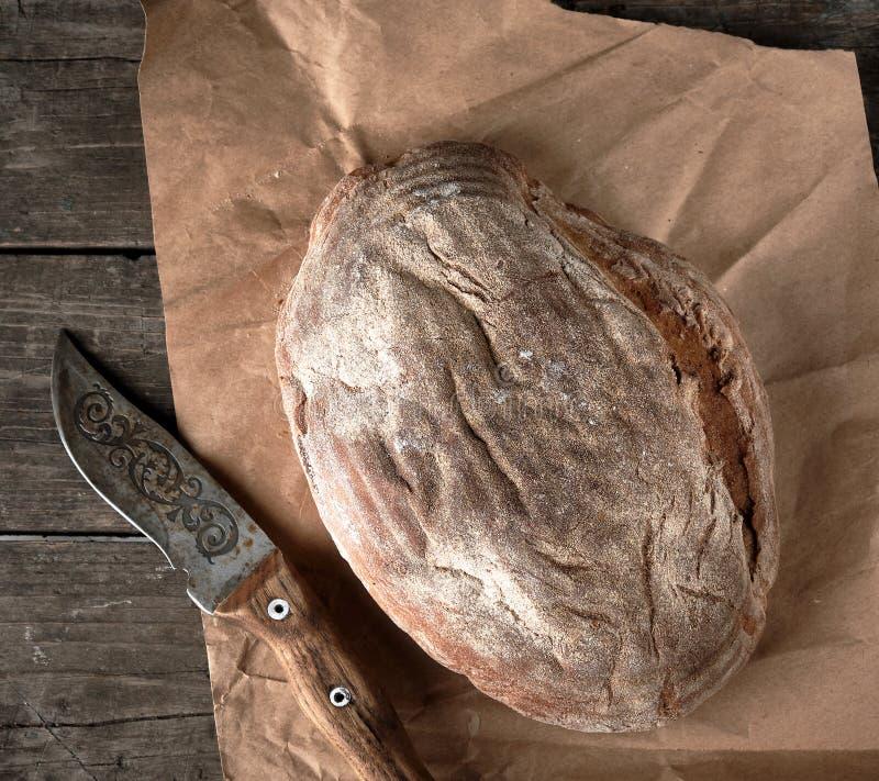 gebakken kernachtig ovaal brood en uitstekend mes stock afbeeldingen