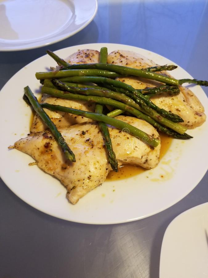 Gebakken kip met boter, zout, peper en asperge stock foto