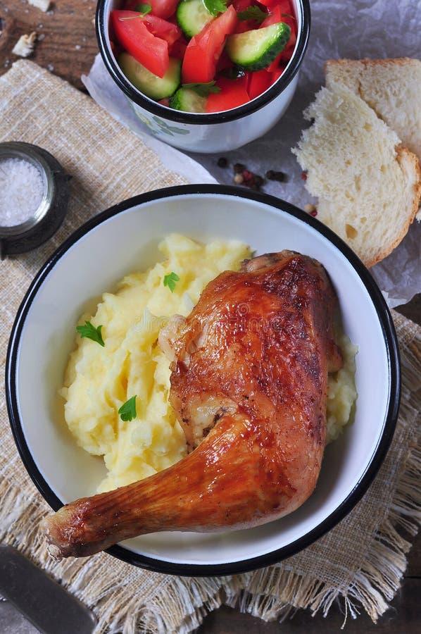 Gebakken kippenbeen met fijngestampte aardappels en plantaardige salade op een houten lijst Selectieve nadruk Rustieke stijl stock foto's