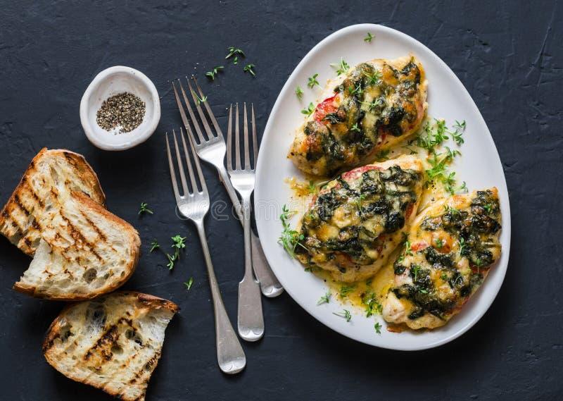 Gebakken kippenborst met tomaten, spinazie en mozarella - heerlijke dieetlunch in mediterrane stijl op een donkere achtergrond royalty-vrije stock foto's