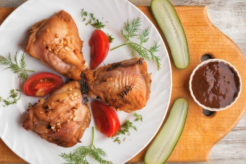 Gebakken kippendijen, groenten en saus op een houten achtergrond stock foto's