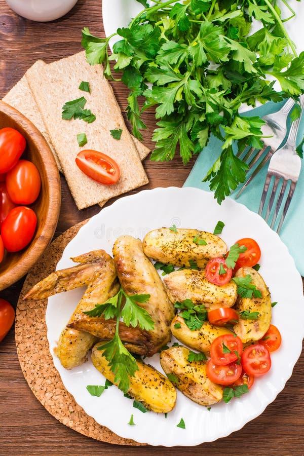 Gebakken kippenvleugels en aardappels, verse tomaten en greens royalty-vrije stock fotografie