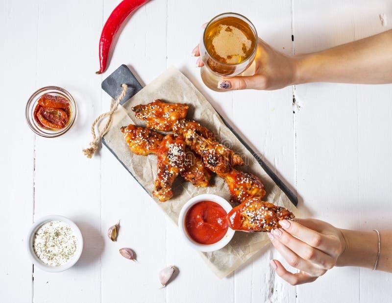 Gebakken kippenvleugels met saus op witte houten achtergrond De greepglas van vrouwenhanden bier royalty-vrije stock afbeelding
