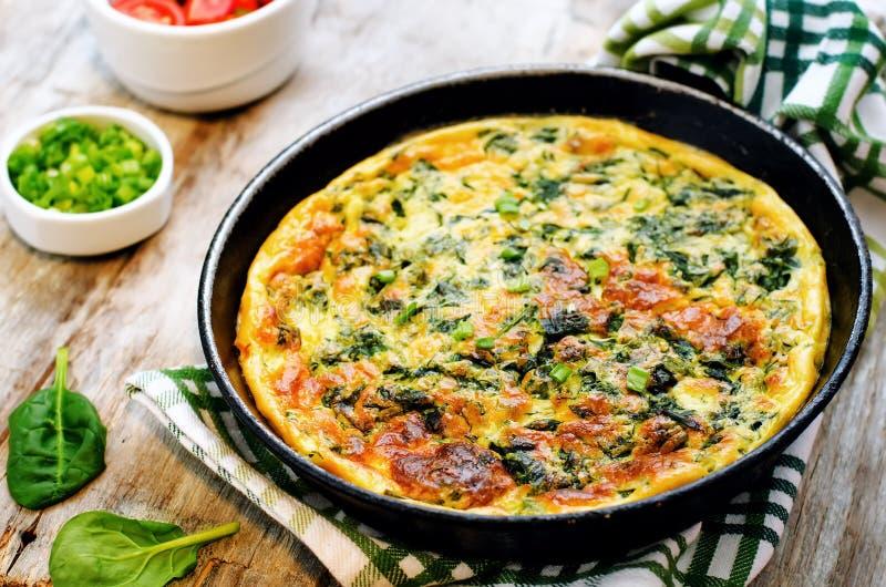 Gebakken omelet met spinazie, dille, peterselie en groene uien stock afbeeldingen