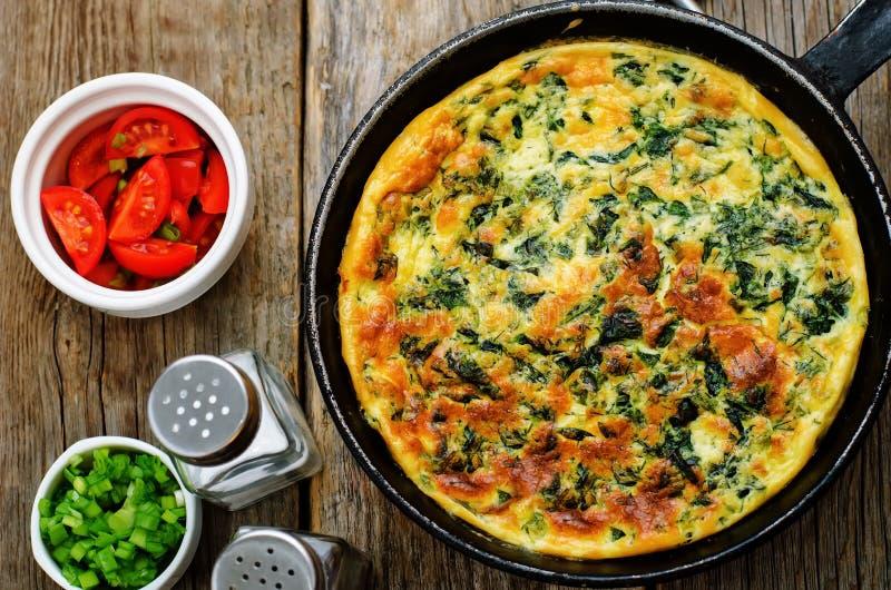 Gebakken omelet met spinazie, dille, peterselie en groene uien stock foto