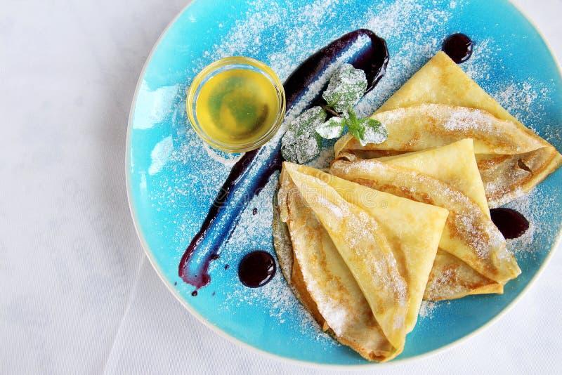 Gebakken pannekoeken met munthoning gepoederde suiker en saus op blauwe plaat stock fotografie