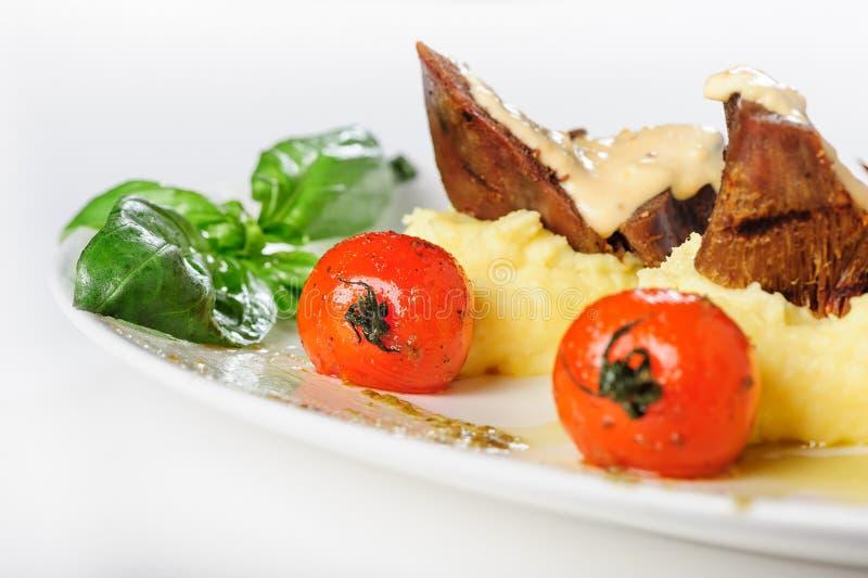 Gebakken schaapvlees met romige saus, fijngestampte aardappel en kersentomaten royalty-vrije stock foto
