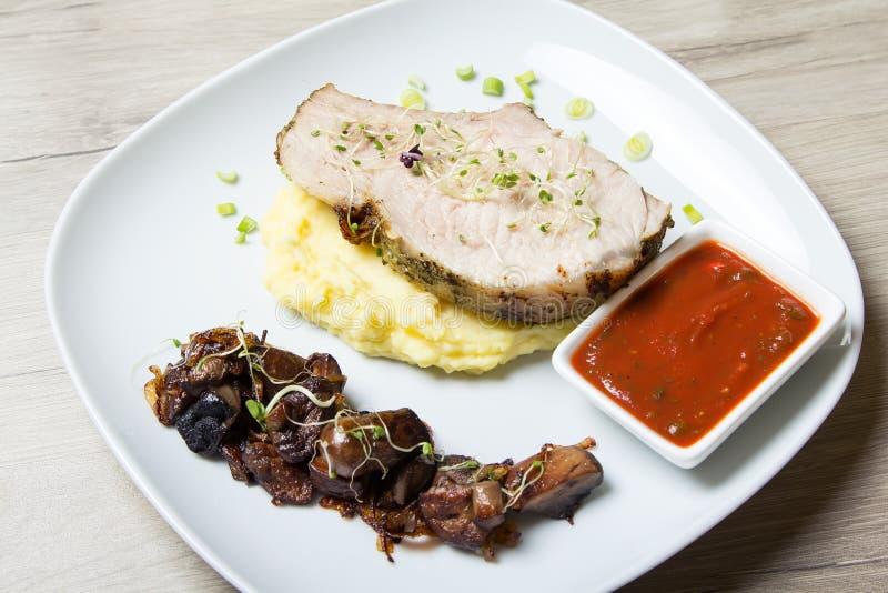 Gebakken varkensvlees met fijngestampte aardappels, gebraden paddestoelen en tomatensaus stock afbeelding