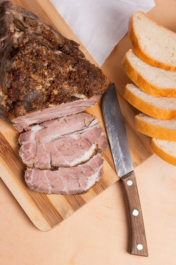 Gebakken varkensvlees met kruiden en kruid op houten raad en en plakken w stock afbeelding