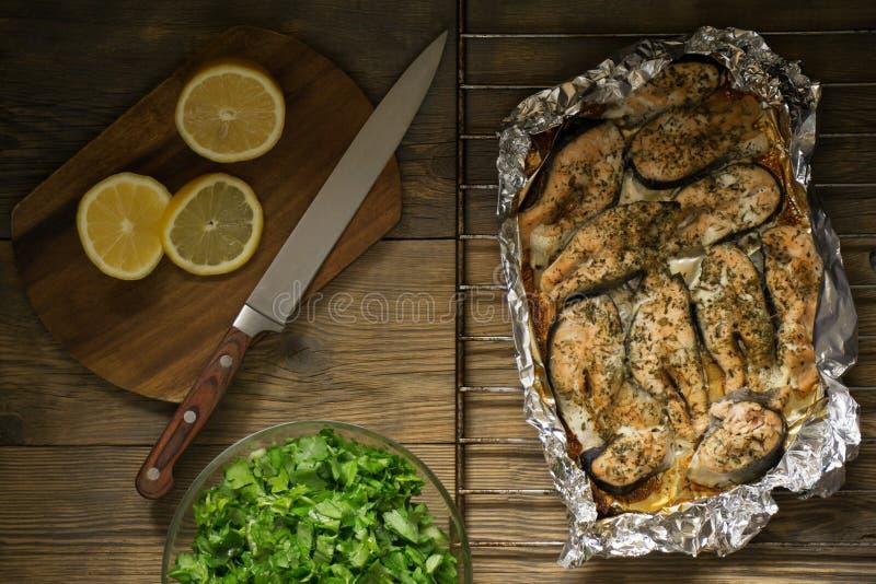 Gebakken vissen met citroen en greens stock foto